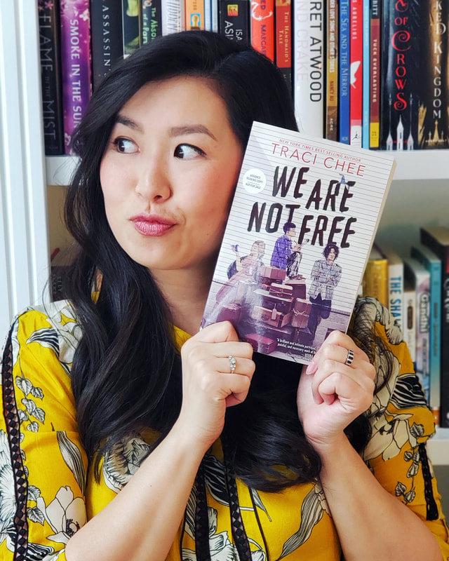 Traci Chee in a yellow floral blouse holding up a copy of her book We Are Not Free