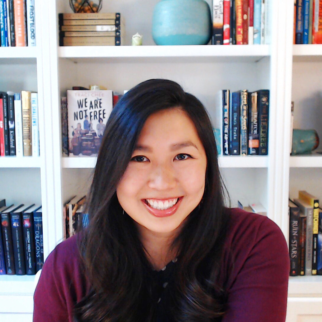 (image: Traci Chee in a magenta smiling with excitement with colorful shelves of books behind)