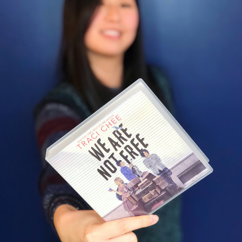 (image: Traci Chee, blurred in the background, holding up a CD copy of We Are Not Free in the foreground)