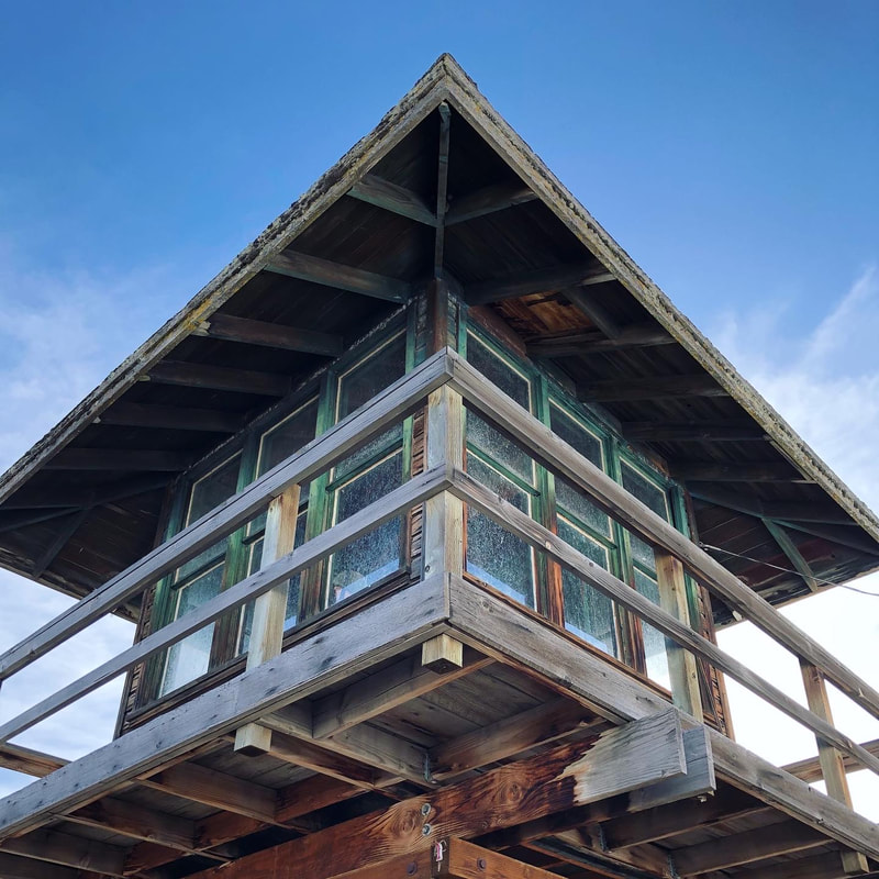 A view of a wooden guard tower from below against a vivid blue sky