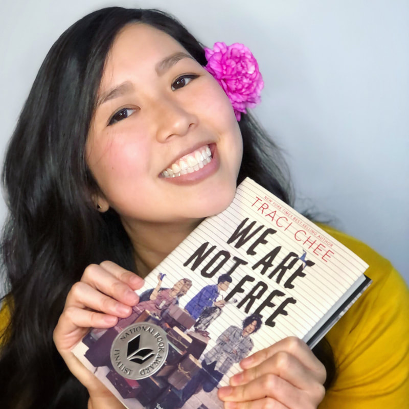 Traci Chee in a yellow sweater with a pink flower behind her ear smiling with a copy of We Are Not Free