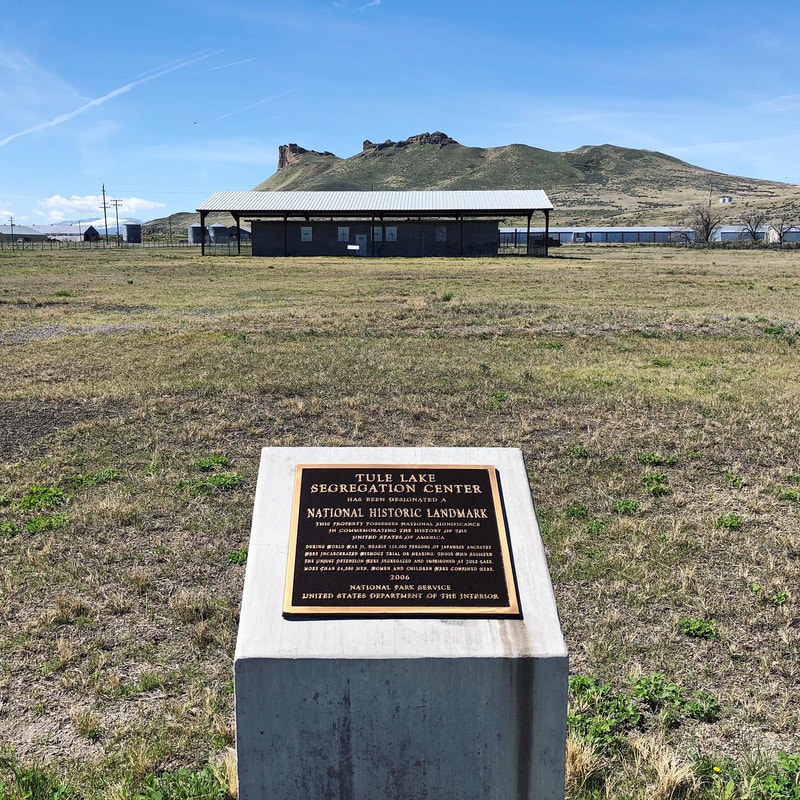 A memorial plaque on a dry grassy plain with a squat concrete building beneath an awning and a rugged mountain in the background