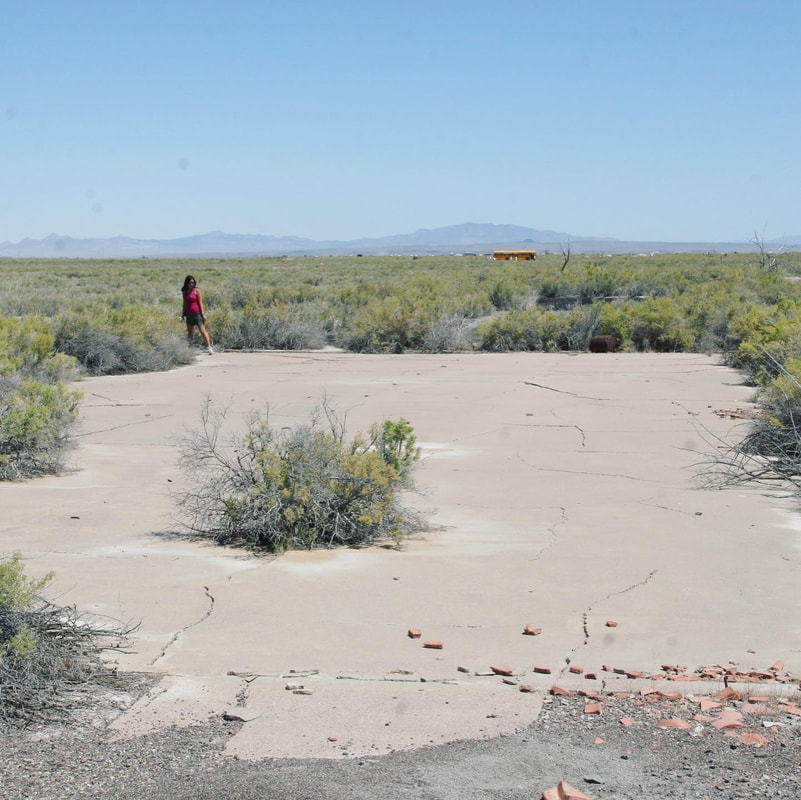 A small female figure in pink standing beside a cracked concrete slab in a scrubby high desert location