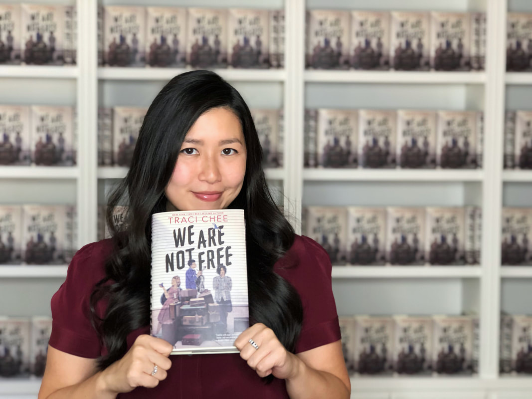 Traci Chee in a burgundy blouse holding up a copy of her book We Are Not Free with bookshelves of We Are Not Free behind