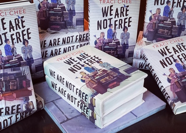 stacks of the book We Are Not Free by Traci Chee surrounding another stack of We Are Not Free that might actually be a cake in disguise