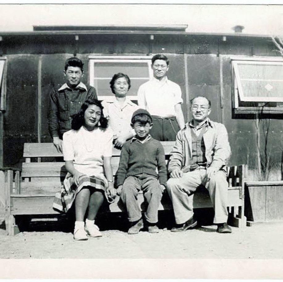 A black and white photo of a Japanese American family sitting on a handmade bench outside of a tar-paper barrack with a potted dead tree behind them