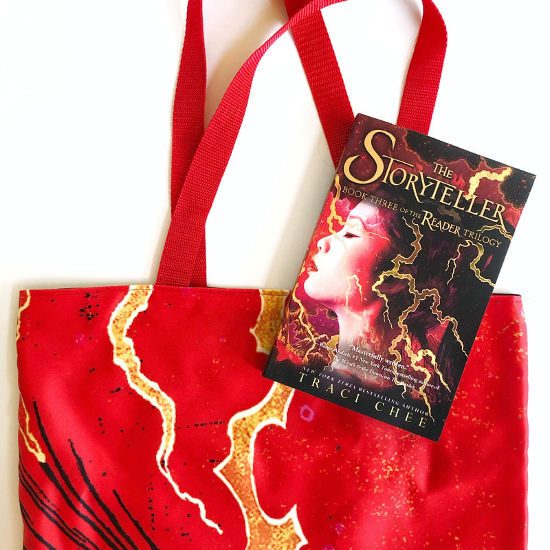 blazing red tote bag with a paperback copy of The Storyteller by Traci Chee