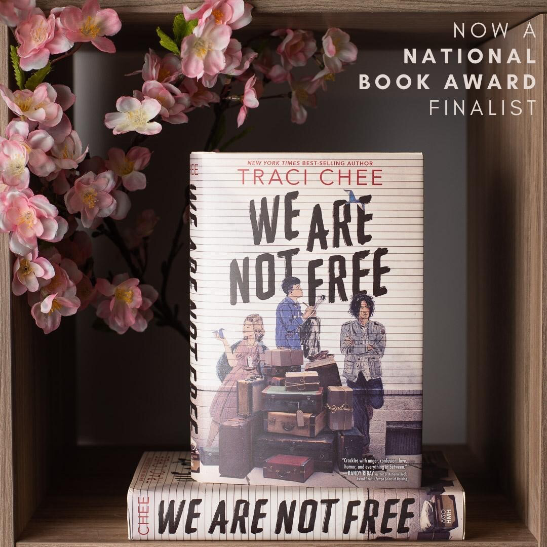 photo of We Are Not Free by Traci Chee in a bookshelf nook with a spray of pink cherry blossoms and the text,