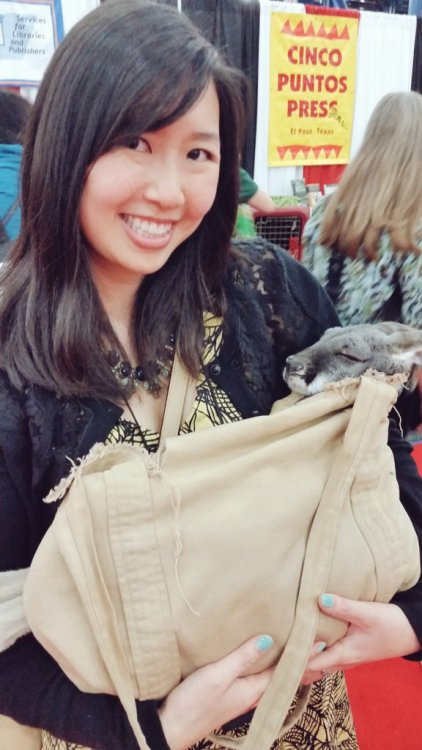 photo of Traci Chee holding a baby kangaroo in a satchel