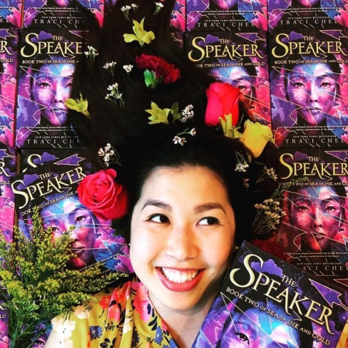 photo of Traci Chee with pink and yellow flowers in her hair, surrounded by copies of THE SPEAKER